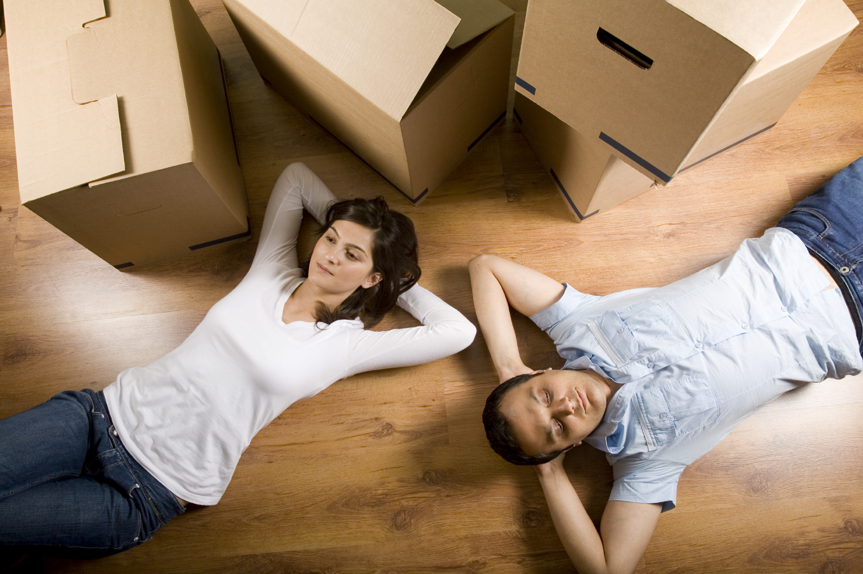 Couple resting after unpacking boxes