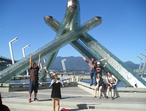 Roots members in front of the Olympic Couldron in Vancouver