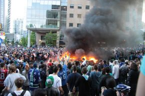 Rioters celebrating openly in front of a burning car in Vancouver