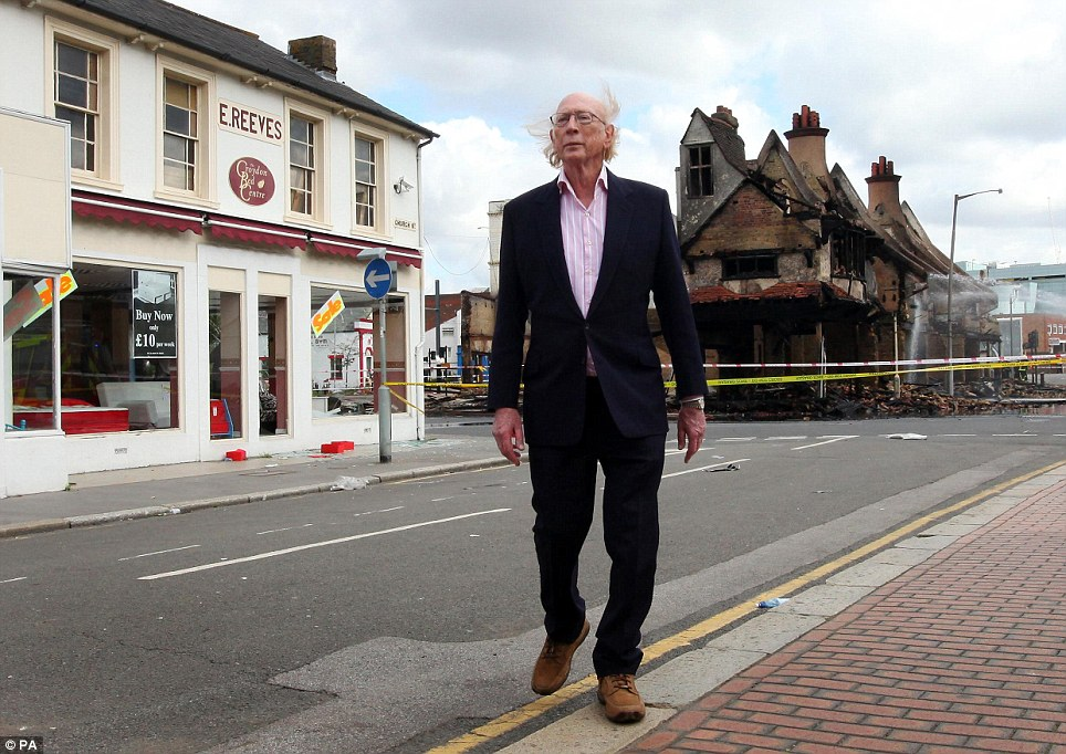 Maurice Reeves outside his burned out 140-year old furniture store in Croydon
