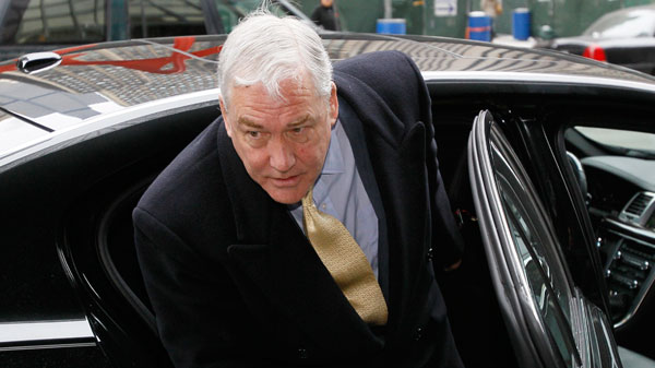 Conrad Black steps out of a black car in Chicago